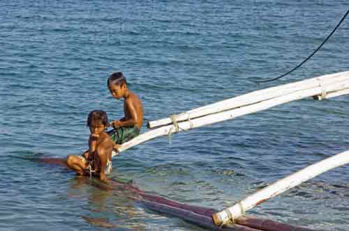 boys sit on outrigger-AsiaPhotoStock
